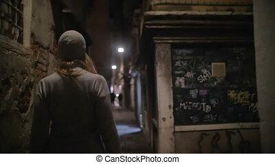 Woman wandering in dark alleyway at night - Slow motion...