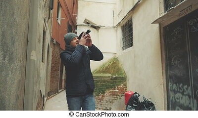 Young man walking outdoor and shooting with retro camera