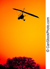Ultra Light Aircraft on Final Approach - The silhouette of...