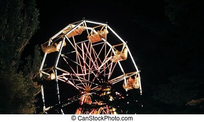 Amusement Park At Night - Ferris Wheel - The brightly lit...