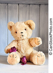 Teddy bear and roses - Old teddy bear with roses sitting in...