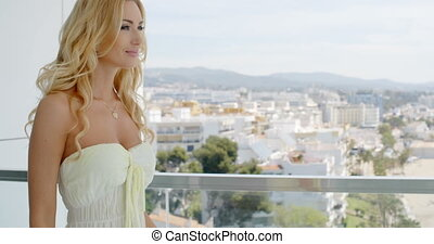 Blond Woman Admiring City View from Balcony