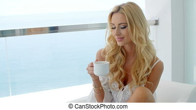Blond Woman Holding Mug and Admiring VIew of Ocean - Smiling...