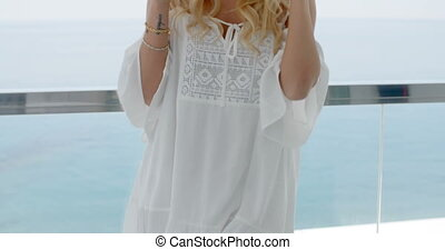 Blond Woman Drinking Coffee on Ocean Front Balcony - Close...