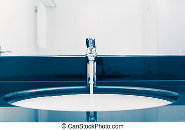 washbasin with faucet and flowing water, blue tone