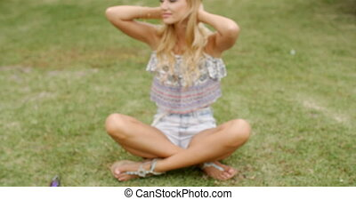 Pretty Blond Woman Sitting on Grassy Ground - Close up...