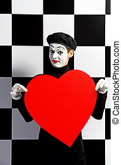 love simbol - Portrait of a male mime artist holds large red...