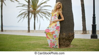 Blond Woman in Sun Dress Leaning Against Palm Tree - Full...