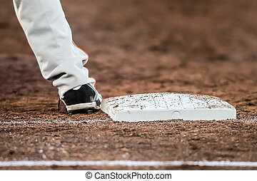 Baseball, player, with, he's, feet, touching, the, base,...