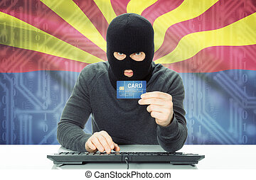 Hacker holding credit card and USA state flag on background...