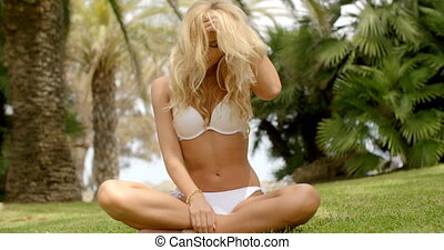 Woman in Bikini Sitting Crossed Legged on Grass - Full...