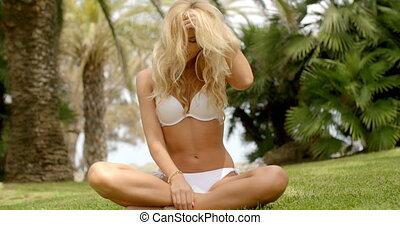 Woman in Bikini Sitting Crossed Legged on Grass - Full...