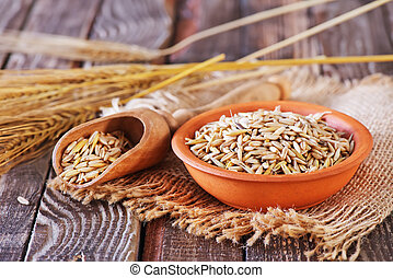 oat grain - dry oat in bowl and on a table