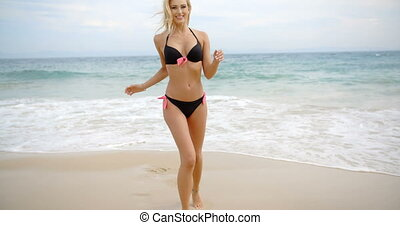 Smiling Blond Woman in Bikini Walking on Beach