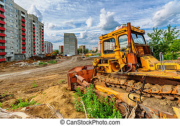 Bulldozer and houses beneath cloudy sky - View of...