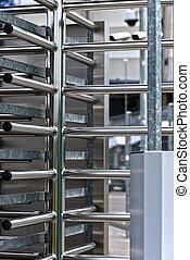 Full-height turnstile guarded stadium entrance. Revolving...