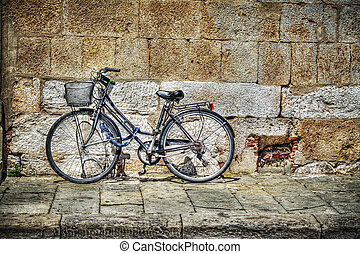 bicycle against a rustic wall in Tuscany