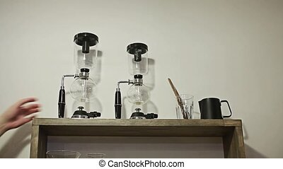 Barista takes vacuum coffee from a shelf2 of those on a...