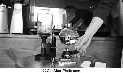 Barista makes vacuum coffee brewing old fashion
