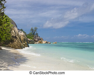 Pristine tropical beach surrounded by granite boulders -...