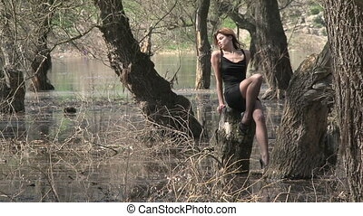 Pretty Model In Sexy Pose On Stump At Park In Flood