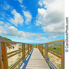 wooden boardwalk in Capo Testa - wooden boardwalk under a...
