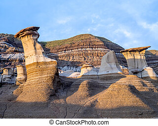 Hoodoos bathed in the warm light of a summer sunset at...