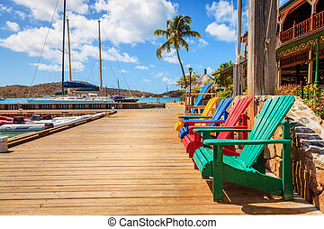 Dockside lounge - Brightly colored adirondack chairs on a...