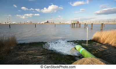 Wastewater Pipe And Refinery - A wastewater pipe and a large...