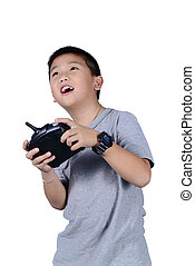 Little boy holding a radio remote control for helicopter,...