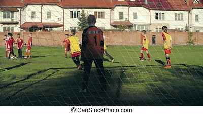 Game Dynamics - Rear view of the goalkeeper keeping the ball...