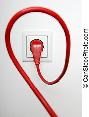 Red power cable plugged in electric outlet, on white...