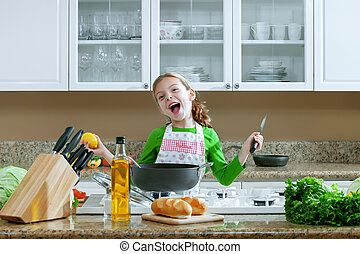 joy - view of young beautiful girl cooking at the kitchen