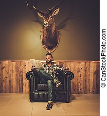 Middle-aged hipster reading newspaper on leather chair will...