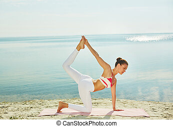 Yoga at leisure - Sporty female doing yoga exercise for...