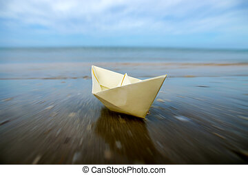 Motion into the sea of paper boats on beach.