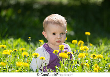 Portrait of the serious little girl among the blossoming...