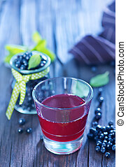 blueberry juice in glass and on a table