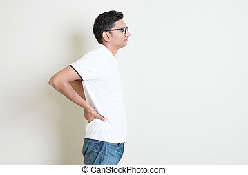 Backpain - Portrait of Indian guy back pain, holding spine...