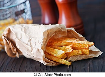 fried potato in paper bag and on a table