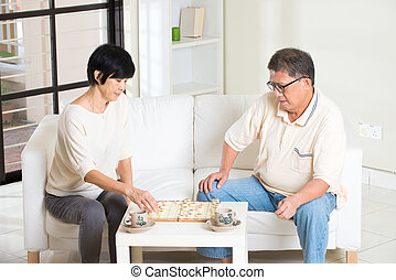 asian senior couple playing chess at home