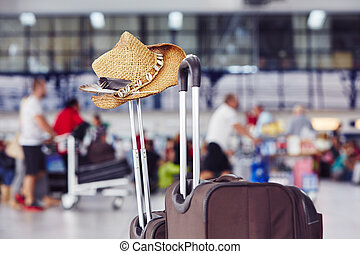 Luggage with straw hat at the airport terminal