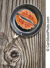 Prosciutto Rashers in Teflon Frying Pan on Old Knotted...