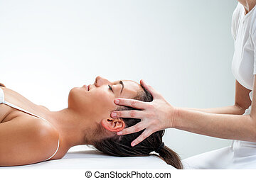 Therapist doing healing osteopathic treatment on woman -...
