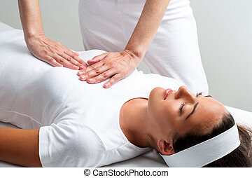 Therapist pressing with hands on womans chest at reiki...