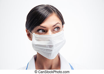 Female medical doctor in mask looking away isolated on a...