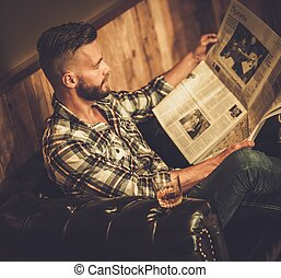 Middle-aged hipster reading newspaper on leather sofa in...