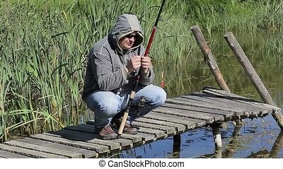 Fisherman on footbridge at the lake in summer