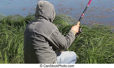 Man with fishing rod at the lake in summer