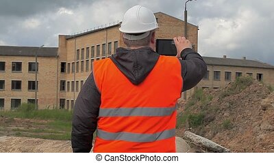 Construction inspector filming with